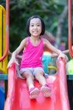 Asiatisk kinesisk liten flicka som spelar p? glidbanan royaltyfri bild