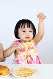 Asiatisk kinesisk liten flicka som äter fransmansmåfiskar Arkivfoto