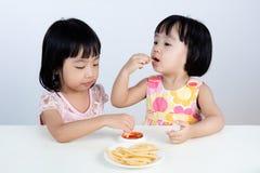 Asiatisk kinesisk liten flicka som äter fransmansmåfiskar Royaltyfri Fotografi