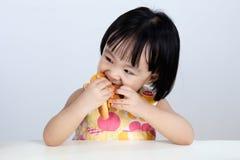 Asiatisk kinesisk liten flicka som äter hamburgaren Fotografering för Bildbyråer