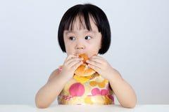 Asiatisk kinesisk liten flicka som äter hamburgaren Arkivfoto