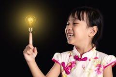 Asiatisk kinesisk liten flicka som upp till pekar den ljusa kulan för finger arkivbilder