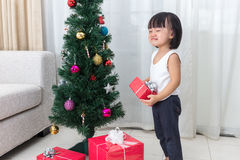 Asiatisk kinesisk liten flickagråt bredvid julgranen Arkivbilder