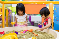 Asiatisk kinesisk liten syster Playing Kinetic Sand inomhus fotografering för bildbyråer