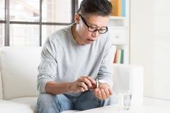 Asiatisk kinesisk man för mogen 50-tal som äter medicin Arkivfoto
