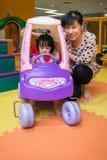 Asiatisk kinesisk moder och dotter som kör leksakbilen på lekplatsen Fotografering för Bildbyråer