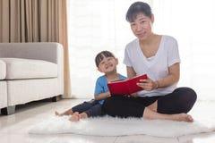 Asiatisk kinesisk moder- och dotterläsning på golvet royaltyfria bilder