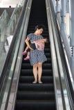 Asiatisk kinesisk moder som bär sova dottern som tar rulltrappan fotografering för bildbyråer