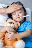 Asiatisk kinesisk moder som mäter liten flickapannan för feber royaltyfria foton