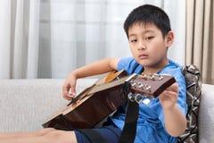 Asiatisk kinesisk pys som spelar gitarren på soffan royaltyfria foton