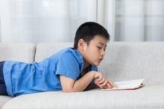 Asiatisk kinesisk pysläsebok på soffan royaltyfri bild