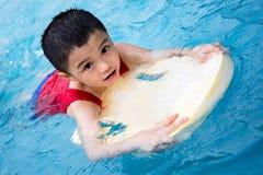Asiatisk kinesLittle Boy simning med att sväva brädet Fotografering för Bildbyråer