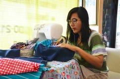 Asiatisk kläder för sömnad för kvinnabruksmaskin Arkivbilder