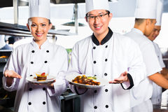 Asiatisk kock i restaurangkökmatlagning royaltyfria foton