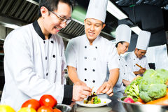 Asiatisk kock i restaurangkökmatlagning Arkivfoto