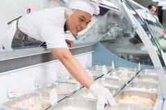 Asiatisk kock som förlägger mat in i en glass räknare Arkivbild