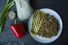 asiatisk kokkonst Sallad av cellofannudlar som stekas med grönsaker som dekoreras med gräsplaner och krabbapinnar Funchoza riktig royaltyfri bild