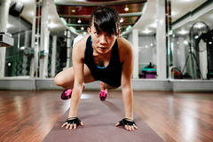 Asiatisk konditionflicka som sträcker i idrottshall Arkivfoton