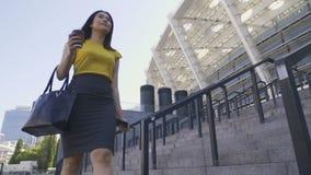 Asiatisk kontorsarbetare med kaffe på vägen att arbeta stock video