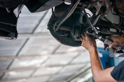 Asiatisk kontrollerande Bush-bult för auto mekaniker under dubbel gaffelbenupphängning vid handen med hjälpmedelbilelevatorn arkivbild
