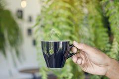 Asiatisk kopp för svart för manhandinnehav av varmt kaffe med att ånga Arkivfoton