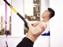 Asiatisk kroppbyggmästare som övar i idrottshall Royaltyfri Foto