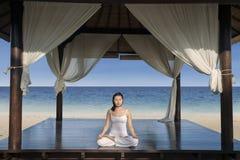 Asiatisk kvinnaövningsyoga på den lyxiga strandsemesterorten Royaltyfri Bild