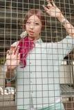 Asiatisk kvinna bak ett metallstaket Royaltyfria Bilder