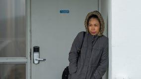 Asiatisk kvinna bundeled upp i anorakanseende bredvid den vita väggen arkivfoto