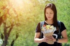 Asiatisk kvinna en bukett av blommor i handen Arkivfoton