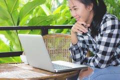 Asiatisk kvinna för affär som arbetar med bärbara datorn och ser i bildskärm royaltyfri foto