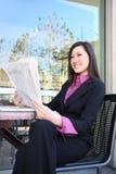 asiatisk kvinna för avläsning för affärstidning Arkivfoto