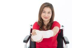 Asiatisk kvinna för bruten arm med gipsförbandet i henne händer som sitter på arkivfoton