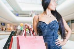 Asiatisk kvinna för Closeupmode som rymmer stora påsar på köpcentret Arkivbild