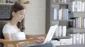 Asiatisk kvinna för härlig stående som arbetar online-bärbara datorn med leende och lyckligt sammanträde på soffan på vardagsrum