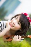 Asiatisk kvinna för härligt leende med ukulelet i trädgård Royaltyfri Fotografi
