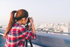 Asiatisk kvinna för långt hår som tar cityscapefotoet på byggnadstak i läge för lågt ljus Fotografi- eller hobbybegrepp Med kopia Arkivbild