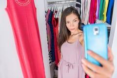 Asiatisk kvinna för Smartphone selfie i klädgarderob fotografering för bildbyråer