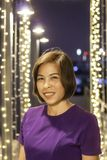 Asiatisk kvinna för stående som ler bakgrundsbelysning arkivbilder