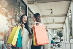 Asiatisk kvinna för två personer som är rolig och som är lycklig om shopping på outen fotografering för bildbyråer