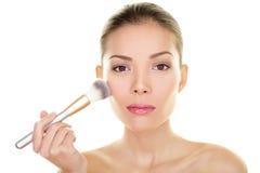 Asiatisk kvinna för makeupskönhet som applicerar rodnad på framsida Arkivbild