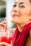 Asiatisk kvinna, i att dricka för restaurang Arkivbild