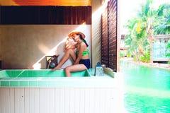 Asiatisk kvinna i bikinin som poserar på bubbelpoolpöl i semesterort Resa resväskan med seascapeinsida Skönhet och sommar arkivbild