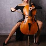 Asiatisk kvinna i en aftonklänning som spelar violoncellen royaltyfria foton
