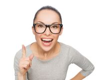 Asiatisk kvinna i glasögon med fingret upp Arkivfoto
