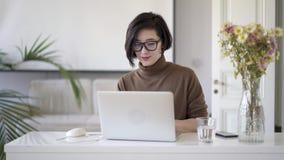 Asiatisk kvinna i glasögon som skriver i bärbar dator i den vita inrikesdepartementet stock video