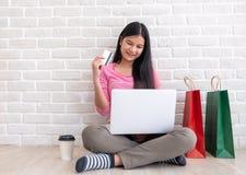 Asiatisk kvinna i hållande kreditkort för rosa tillfällig torkduk och användal fotografering för bildbyråer