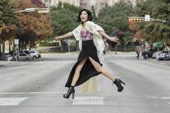 Asiatisk kvinna i livsstillägen som framme korsar gatagatan av huvudbyggnad i Austin, Texas arkivfoto