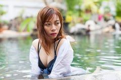 Asiatisk kvinna i lopp för semester för hotellsimbassäng avslappnande, ung flicka som tycker om Spa royaltyfri foto