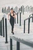 Asiatisk kvinna i sportswearen som är rinnande upp på stadiontrappa arkivbilder